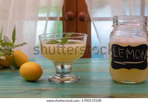 A glass of lemon juice and mint leaves on the kitchen window