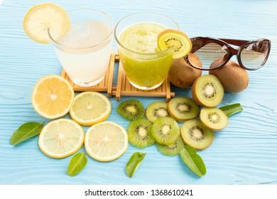 glass of lemon juice white lime and kiwi juice on blue wood background