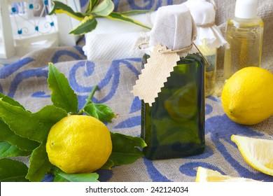 A glass of lemon oil. Fresh lemon fruits in the background