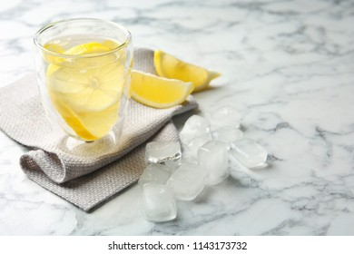 Glass with lemon water and ice cubes on marble table