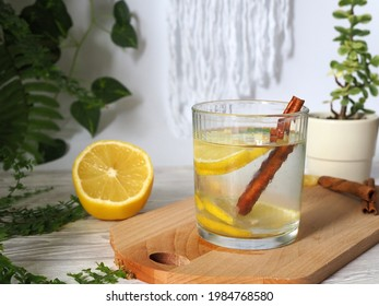 Glass of lemonade with lemon, drink with cinnamon stick on a wooden board. In the background green leaves