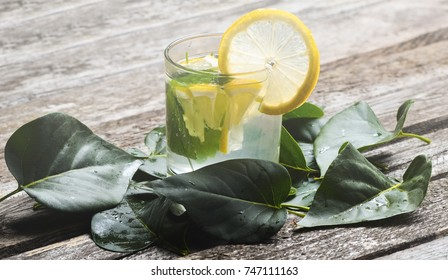 A glass of lemonade with lemon and melissa on wooden texture boards with lying fallen green leaves. Non-alcoholic mojito.