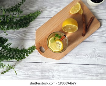 Glass of lemonade with lemons, drink with cinnamon stick on a wooden board