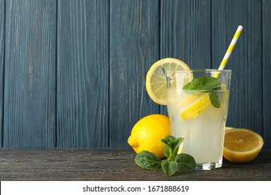 Glass with lemonade and lemons on wooden background. Fresh drink