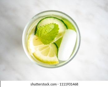 Glass of lemonade made from lemon, lime and cucumber with ice cubes. Overhead close up.