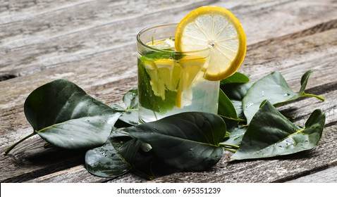 A glass of lemonade with melissa on a wooden table. Fallen green leaves on wooden texture boards.