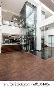 Glass lift and wooden stairs leading to the lobby in university building