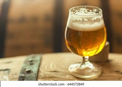 Glass of light barrel aged beer standing on an oak wood barrel