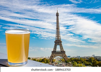 Glass of light beer against Paris skyline with Eiffel tower background.