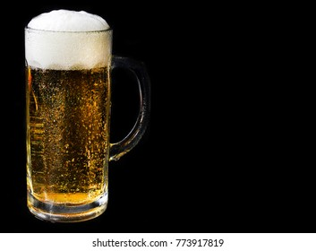 A glass of light beer close-up on a black background