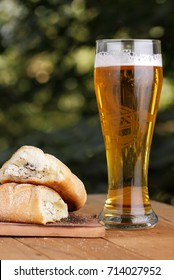 A glass of light beer with a curd Greek pie in the open air