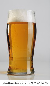 A glass of light beer on gray background.