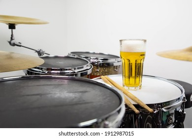 Glass of light beer on professional drum set closeup. Drumsticks, drums and cymbals, at live music rock concert, in the club stage, bar, or in recording studio.  White background.