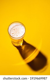 Glass of light beer on a yellow background, top view. Shadow from a glass of lager.  - Shutterstock ID 1919669987
