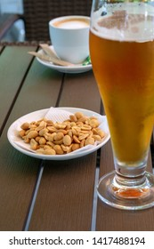 Glass with light beer, roasted peanuts and a cup of americano on a wooden table. Soft focus