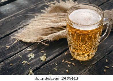 Glass of light beer with scattered around hop and malt and rye ears on aged wooden table background.
