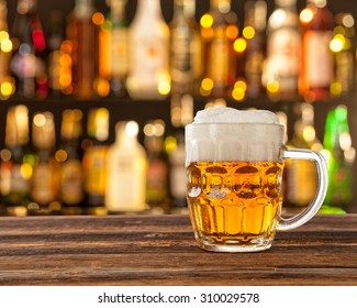 Glass of light beer served on wooden desk. Bar on background