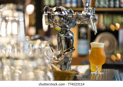 Glass of light beer, serving fresh beer in bar counter.