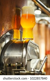 Glass of light beer standing on a piece of brewing equipment in an operating brewery