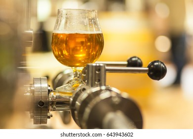 Glass of light beer standing on a stainless steel line with valves in a production brewery