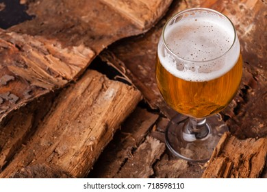 Glass of light beer standing on a pile of dry wood bark