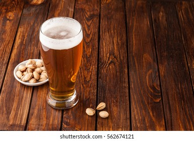 glass of light cold frothy beer, nuts on an old wooden table