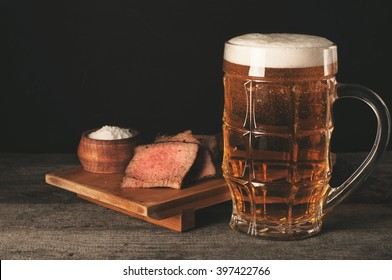 Glass of light foam beer with meat appetizer on a wooden table on a black background
