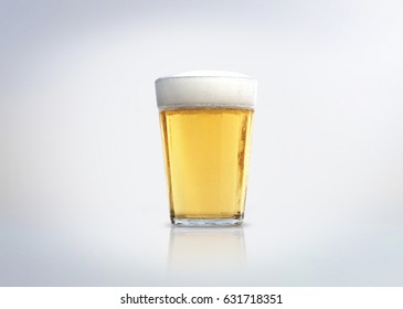 Glass of light lager beer with foam. Isolated on white background.