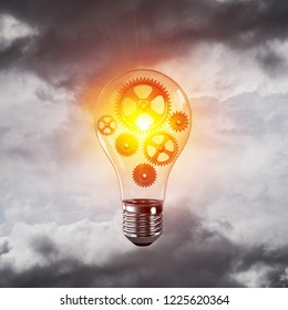 Glass lightbulb with multiple gears inside with grey cloudly skyscape on background. 3D rendering.