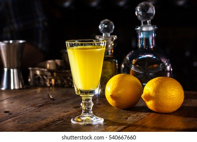 A glass of Limoncello is on the table in a dark room. In the background the lemons and bottle.