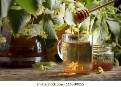Glass of linden tea with honey and flowers on wooden table.