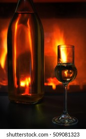 A glass of liqueur and a blurred bottle with liqueur in the background in front of the flames of a burning fireplace on a black table.