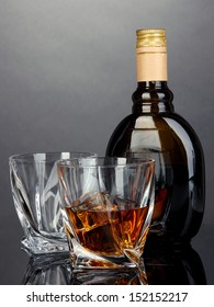 Glass of liquor with bottle, on dark background