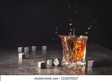 Glass with liquor splash and whiskey stones on table