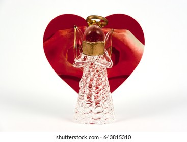 Glass made angel reading. Heart shape red greeting card with love sign made by hands behind it.