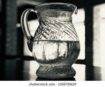 Glass made jug of water on a table isolated object photo