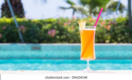 Glass of Mai Tai cocktail on the pool nosing at the tropical resort. Horizontal, wide screen, cocktail on right side