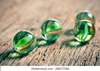 Glass marble balls on old wooden background