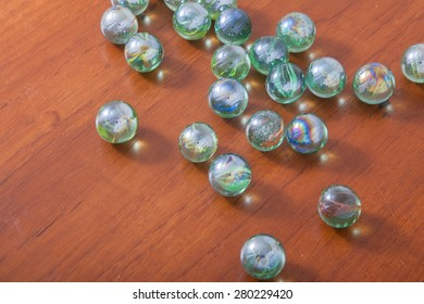 glass marble balls spread on wooden table top