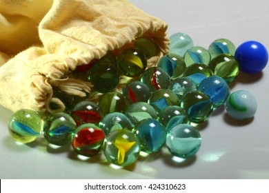 Glass marbles spilling out from a cloth bag