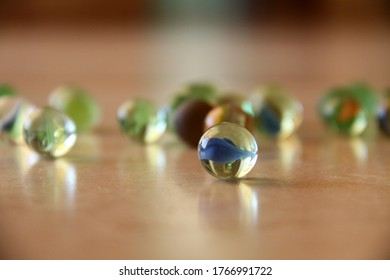 Glass marbles spread on the floor closeup with reflection