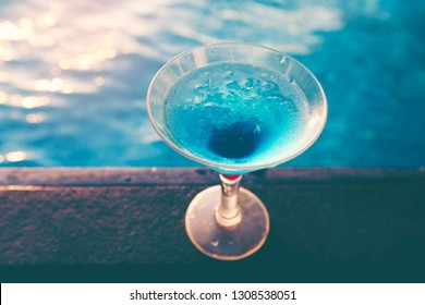 Glass of martini cocktail at swimming pool with ocean and palm tree background. A  glass of blue martini cocktail welcome drink bar.Selective focus. season and holidays concept.