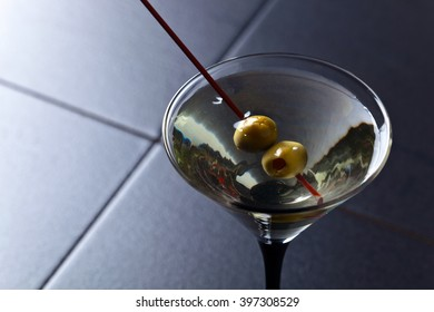 glass of martini , focus on a olives