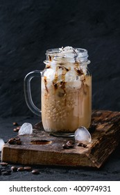 Glass mason jar with ice coffee with whipped cream, ice cream and chocolate sauce, served with coffee beans and ice cubes on wooden chopping board over black textured background.