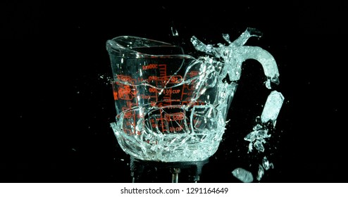 A Glass Measuring Cup Shattering, breaking, exploding into shards on black. Glass handle starting to fall off