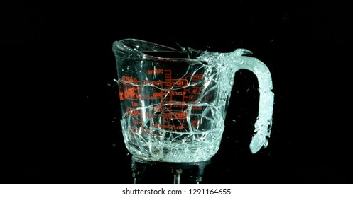 A Glass Measuring Cup Shattering, breaking, exploding into shards isolated on black. Glass almost fully together