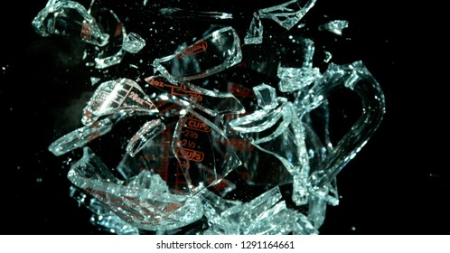 A Glass Measuring Cup Shattering, breaking, exploding into shards on black. Glass really breaking apart from rest.