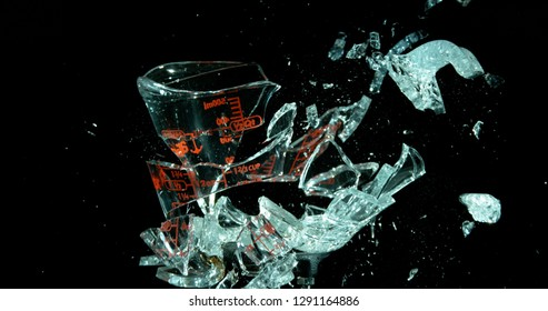 A Glass Measuring Cup Shattering, breaking, exploding into shards isolated on black. Big pieces still together