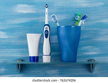 In glass are mechanical toothbrushes, next electric and toothpaste in the bathroom, on blue background