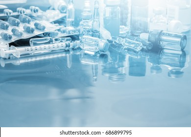 Glass Medicine Vials ampule ,medicine pill and capsule Syringe on x-ray film over doctor table for background with copy space on front area